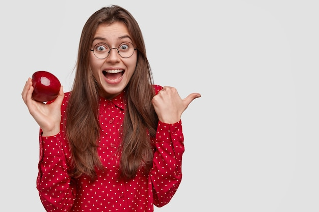 Zdjęcie zadowolonej ciemnowłosej kobiety z radosnym wyrazem twarzy, wskazuje w prawą stronę, nosi soczyste czerwone jabłko
