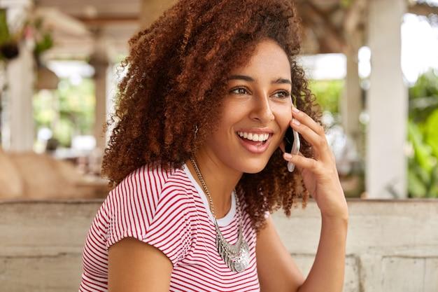 Zdjęcie zadowolonej czarnej kobiety ma krzaczaste kręcone włosy