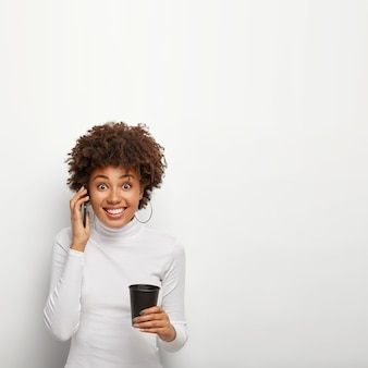 Zdjęcie zadowolonej dziewczyny hipster z kręconymi włosami dostaje dobre wieści podczas rozmowy telefonicznej