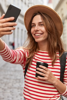 Zdjęcie zadowolonej europejki pozuje do robienia selfie, lubi spacerować po centrum miasta, odpoczywa na świeżym powietrzu