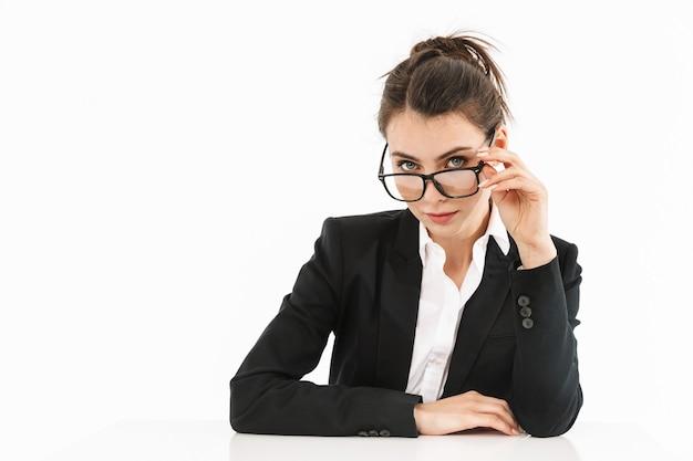 Zdjęcie zadowolonej kobiety-pracowniczki ubranej w strój wizytowy, patrzącej na bok podczas pracy i siedzącej przy biurku w biurze na białym tle nad białą ścianą