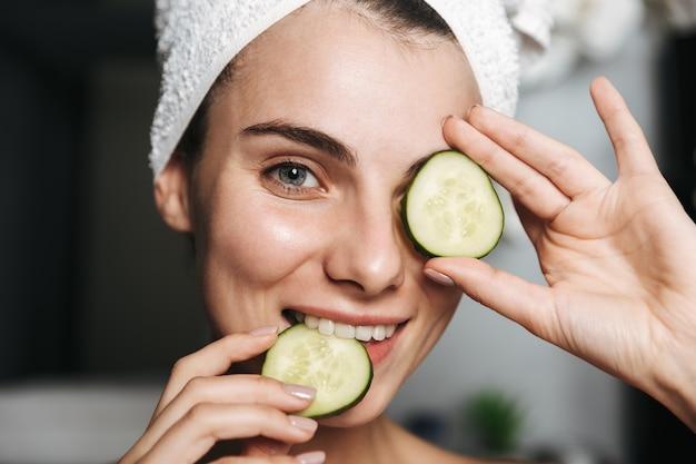 Zdjęcie zadowolonej kobiety z ręcznikiem na głowie trzymając plasterki ogórka na jej twarzy