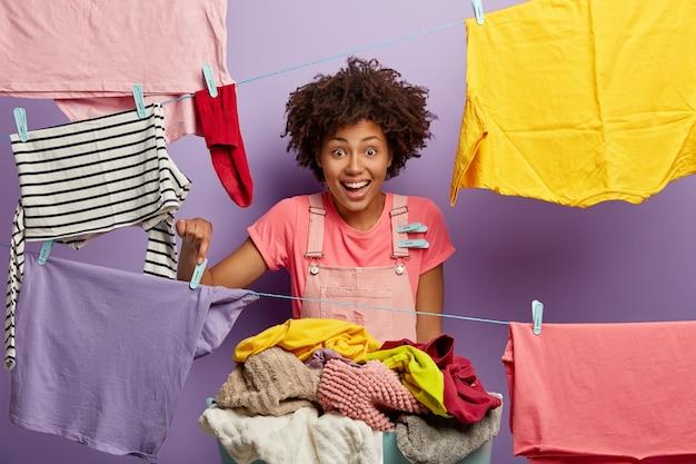 Zdjęcie zadowolonej kobiety zajętej wykonywaniem wielu prac domowych, rozwiesza mokre pranie ze spinaczami do bielizny do wyschnięcia