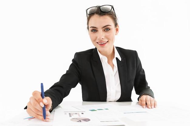 Zdjęcie zadowolonej pracownic bizneswoman ubranej w strój wizytowy, pracującej z papierowymi wykresami, siedząc przy biurku w biurze na białym tle nad białą ścianą