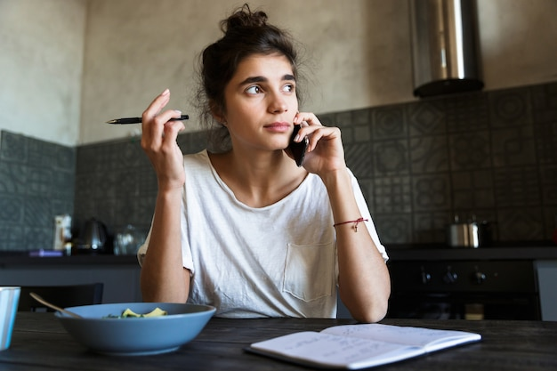 Zdjęcie zadumanej brunetki piszącej w pamiętniku i rozmawiającej przez telefon podczas śniadania w kuchni w domu