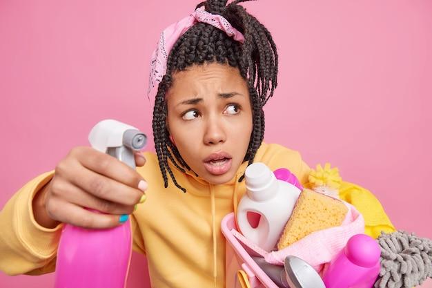 Zdjęcie zaintrygowanej kobiety rasy mieszanej trzyma detergent do mycia okien w koszu ze środkami czyszczącymi