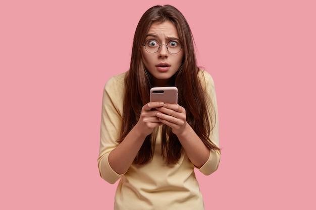 Zdjęcie zaintrygowanej pięknej kobiety ma oburzony wyraz twarzy, trzyma w rękach smartfon, pisze wiadomości, ubrana swobodnie
