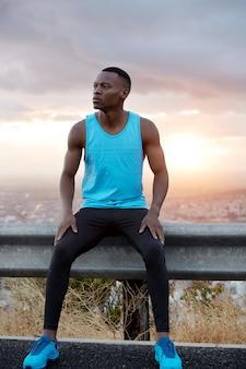 Zdjęcie zamyślonego czarnego mężczyzny w niebieskiej kamizelce, czarnych spodniach i kaloszach, pozuje przy znaku drogowym nad cudownym widokiem wschodu słońca, rano przed pracą ćwiczy jogging. strzał w pionie. wytrzymałość