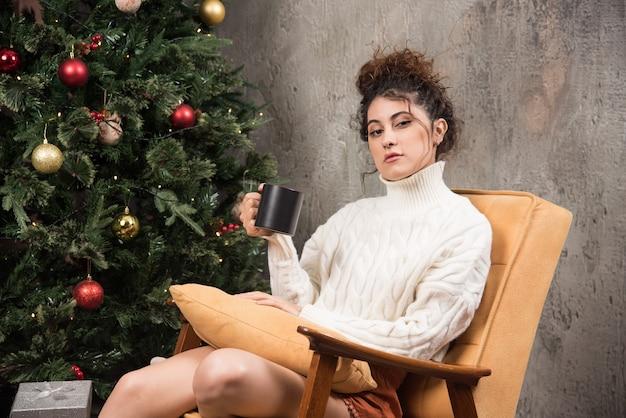 Zdjęcie zamyślonej kobiety siedzącej na wygodnym krześle z filiżanką napoju
