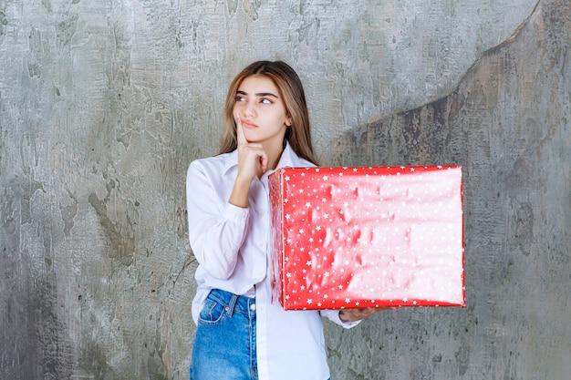 Zdjęcie zamyślonej modelki z długimi włosami trzymającej duży czerwony prezent