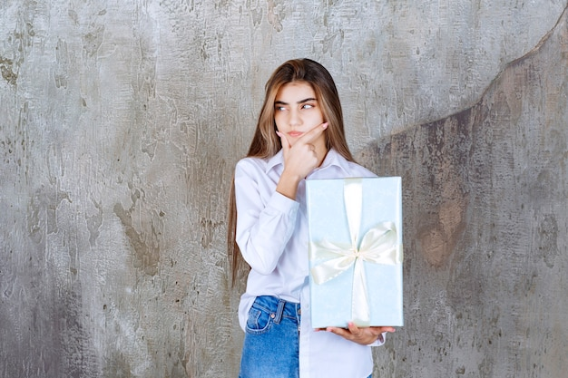 Zdjęcie zamyślonej modelki z długimi włosami trzymającej duży prezent