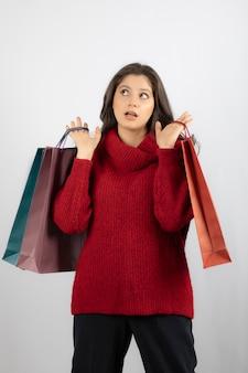 Zdjęcie zamyślonej pani trzymającej kolorowe torby na zakupy.