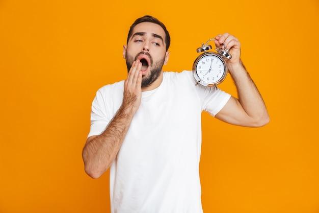 Zdjęcie zaniepokojonego mężczyzny w wieku 30 lat w zwykłym stroju z budzikiem, odizolowane