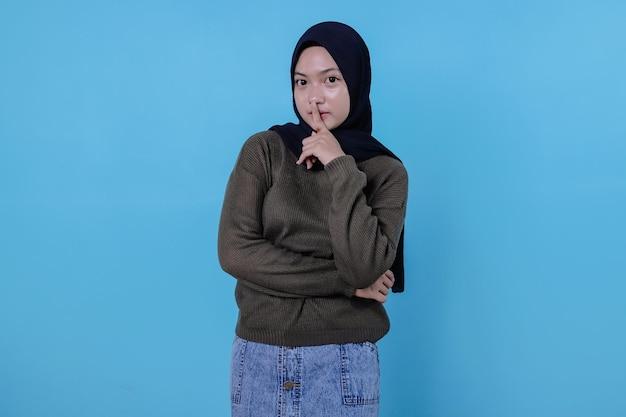Zdjęcie zaskoczonej kobiety w hidżabie trzyma w tajemnicy i prosi o ciszę, przyciska palec wskazujący do ust, pokazuje milczenie