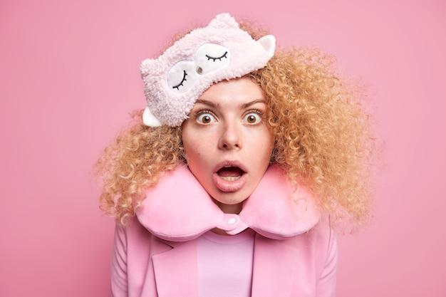 Zdjęcie zaskoczonej kobiety z kręconymi włosami, która patrzy zdziwiona na aparat