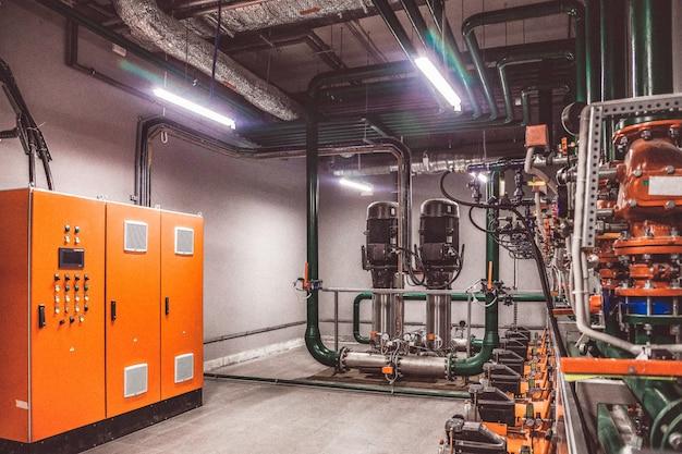Zdjęcie zawiera ziarno filmu. przemysłowe wnętrze pompy wodnej, zaworów, manometrów, silników w maszynowni. zawór i pompy w pomieszczeniu przemysłowym. potężne rurociągi, automatyczne systemy sterowania
