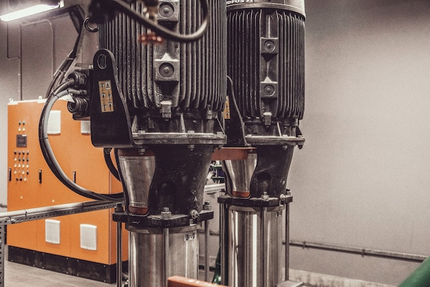Zdjęcie zawiera ziarno filmu. stacja pomp wody i rurociąg ze zbiornikami w pomieszczeniu przemysłowym do dostarczania wody pod wysokim ciśnieniem do zadań gaśniczych. rury tryskaczowe i system sterowania do dostarczania wody pitnej
