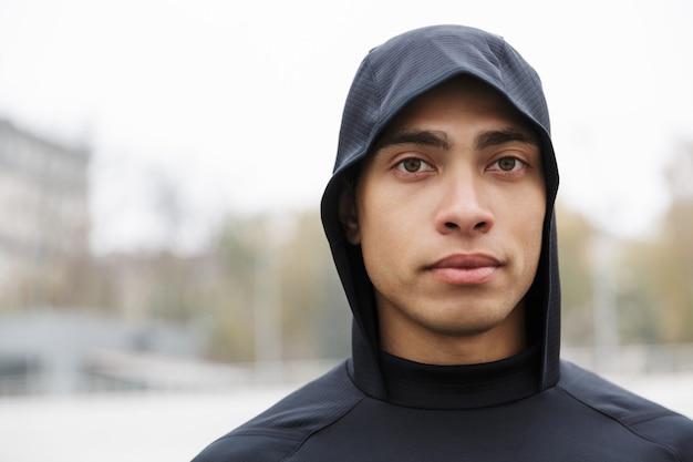 Zdjęcie zbliżenie atletycznego sportowca kaukaskiego w kapturze, stojąc i patrząc na kamerę podczas ćwiczeń na stadionie po deszczu