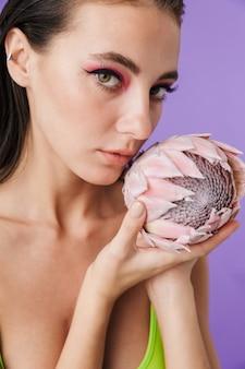 Zdjęcie zbliżenie atrakcyjnej brunetki z jasnym makijażem trzymającej egzotyczny kwiat