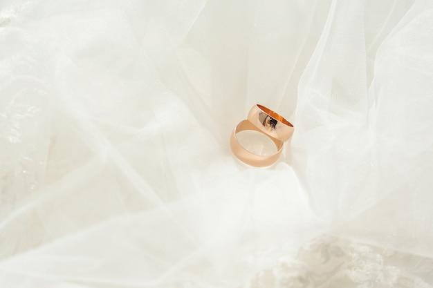 Zdjęcie zbliżenie dwa złote obrączki ślubne.