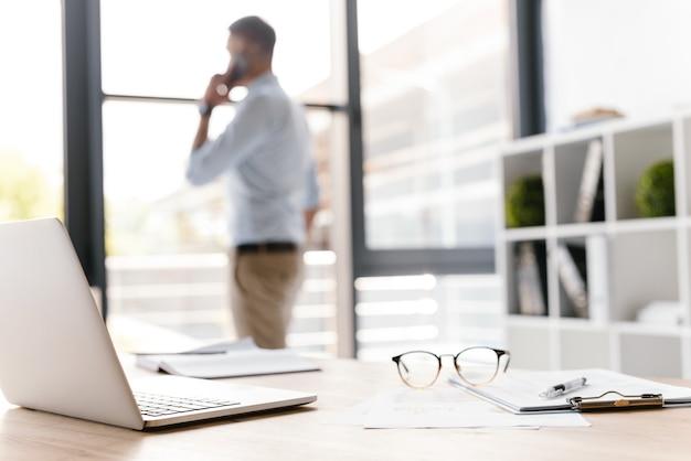Zdjęcie zbliżenie miejsca pracy z biurowymi rzeczami leżącymi na stole, podczas gdy niewyraźny biznesmen mówi na smartfonie i patrząc przez duże okno
