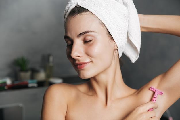 Zdjęcie zbliżenie młodej kobiety z ręcznikiem na głowie do golenia jej pachy z brzytwą