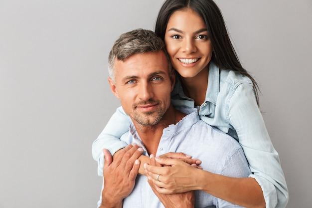 Zdjęcie zbliżenie treści europejczycy mężczyzna i kobieta w podstawowej odzieży uśmiechnięci i przytuleni razem, odizolowane na szaro