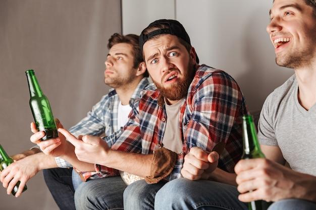 Zdjęcie zdenerwowanego mężczyzny wyrażającego frustrację i niezadowolenie podczas oglądania meczu piłki nożnej w mieszkaniu z kolegami