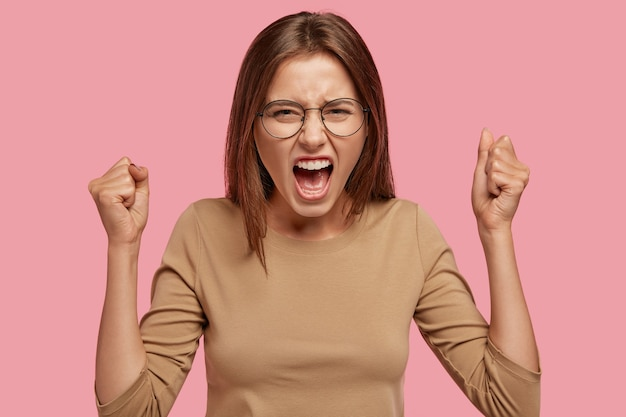 Zdjęcie zdenerwowanej gospodyni domowej, która pokłóciła się z sąsiadem, podnosi ręce zaciśnięte w pięści, krzyczy ze złości
