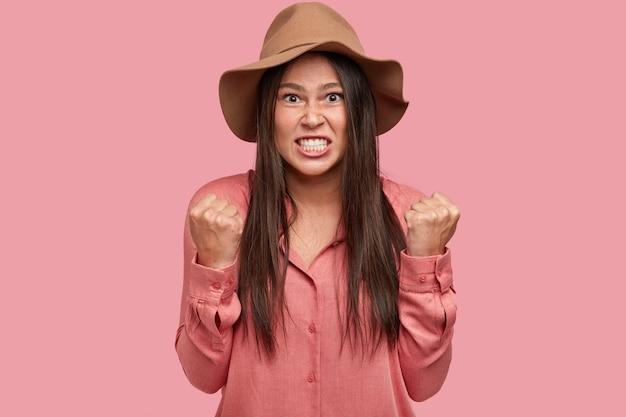 Zdjęcie zdenerwowanej niezadowolonej zrzędliwej dziewczyny zaciska zęby i pięści, wyraża złość tak samo jak kłótnia