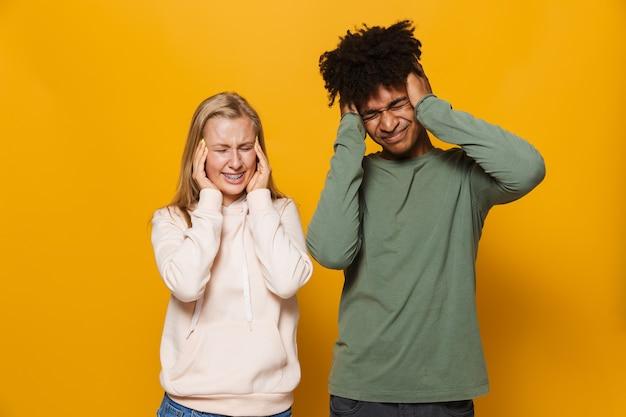 Zdjęcie zdenerwowanej pary mężczyzny i kobiety w wieku 16-18 lat z aparatami ortodontycznymi zakrywającymi uszy, odizolowane na żółtym tle