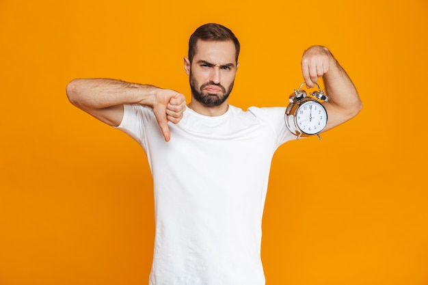 Zdjęcie zdenerwowany mężczyzna 30s w codziennym noszeniu trzymając budzik, na białym tle