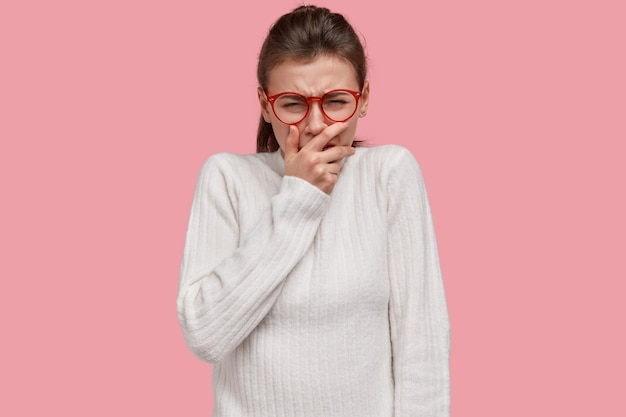 Zdjęcie zdesperowanej kobiety płacze z rozpaczy, ma życiowe porażki, zakrywa usta, wyraża negatywne emocje, nosi swobodny sweter, modelki na różowej ścianie pracowni. ludzie