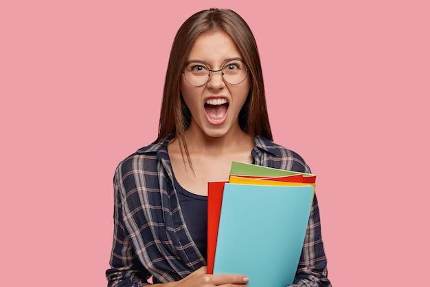 Zdjęcie zdesperowanej, wściekłej kobiety otwiera usta i woła ze złości, czuje się zirytowana
