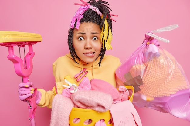 Zdjęcie zdesperowanej, zdenerwowanej afroamerykanki niosącej worek na śmieci