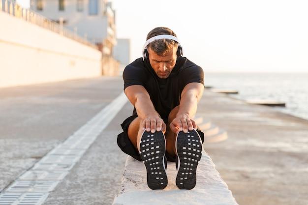 Zdjęcie zdrowego mężczyzny rasy kaukaskiej po trzydziestce w dresie, rozgrzewającego i wyciągającego nogi poza wybrzeżem, podczas słuchania muzyki przez słuchawki bezprzewodowe podczas wschodu słońca