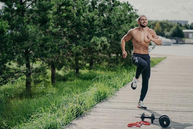 Zdjęcie zdrowego zmotywowanego mężczyzny z grubym włosiem, który wykonuje skoki na świeżym powietrzu i prowadzi zdrowy tryb życia