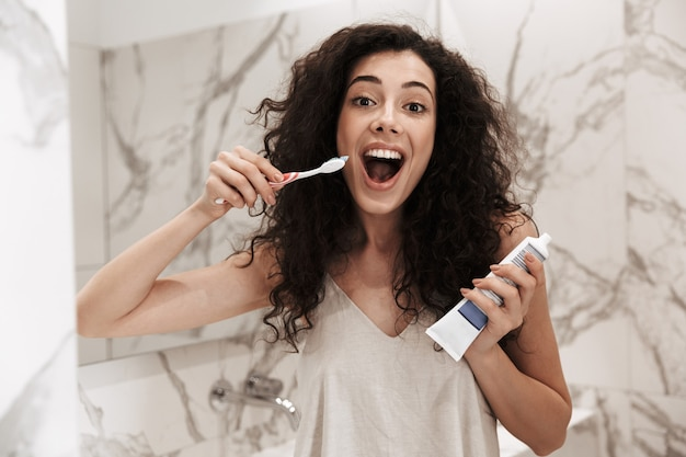Zdjęcie zdrowej atrakcyjnej kobiety o długich ciemnych włosach stojącej w hotelowej łazience i czyszczącej zęby szczoteczką i pastą do zębów
