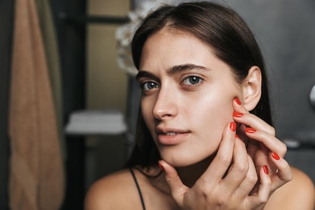 Zdjęcie zdrowej kobiety o długich ciemnych włosach i czystej skórze, patrząc w przyszłość i dotykając jej twarzy