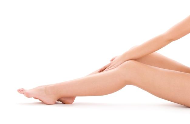 Zdjęcie zdrowych nóg nagiej kobiety na białym