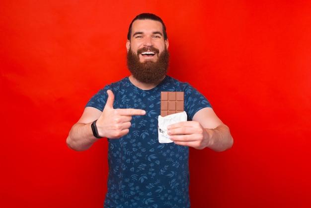 Zdjęcie zdumionego brodatego mężczyzny wskazującego na tabliczkę czekolady na czerwonym tle