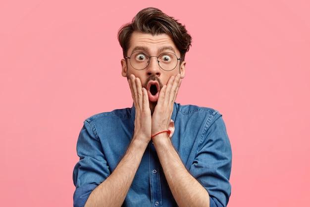 Zdjęcie zdumionego brodatego mężczyzny ze stylową fryzurą trzyma dłonie na obu policzkach, wygląda zaskakująco i zszokowanym, szeroko otwiera usta, ubrany w dżinsową koszulę, pozuje na różowej ścianie
