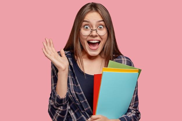 Zdjęcie zdumionej kobiety rasy kaukaskiej trzymającej dłoń blisko twarzy, woła z pewnością, zadowolona z dobrych wyników egzaminu