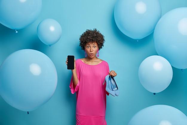 Zdjęcie zdumionej, kręconej młodej kobiety pokazuje wyświetlacz telefonu komórkowego i buty na wysokich obcasach, robi zakupy w internecie, kupuje ubrania w sklepie internetowym, stoi pod niebieską ścianą z balonami dookoła