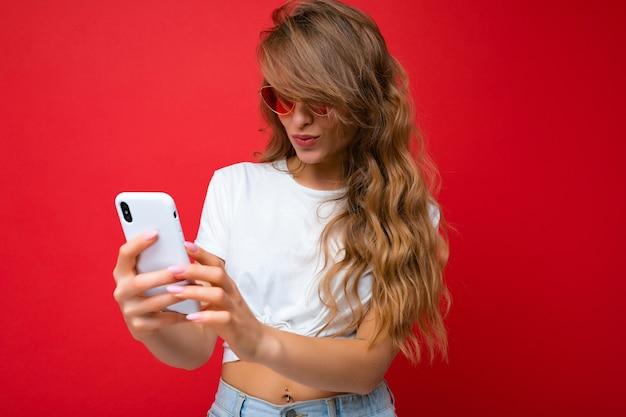 Zdjęcie zdumionej pięknej młodej kobiety trzymającej telefon komórkowy noszącej okulary przeciwsłoneczne codziennie stylowe