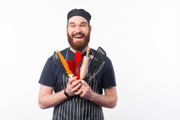Zdjęcie zdumiony brodaty mężczyzna szefa kuchni, trzymając w ręku naczynia