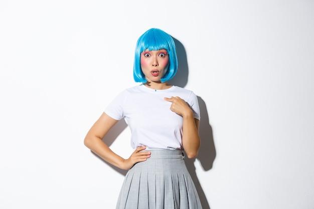 Zdjęcie zdziwionej azjatki, dyszącej, zaskoczonej i wskazującej na siebie palcem, ubranej w niebieską perukę na halloween, stojącej.