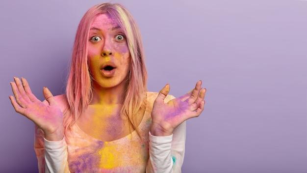 Zdjęcie zdziwionej europejki obsypanej kolorowym proszkiem, spędzającej weekend na festiwalu holi, rozkładającej ręce, otwierającej usta, modelki na fioletowej ścianie, puste miejsce na tekst.