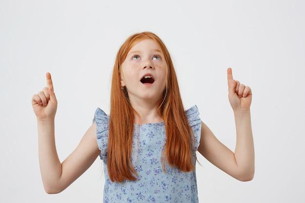Zdjęcie zdziwionej małej rudowłosej dziewczynki z piegami z dwoma ogonami, patrzy w górę i wskazuje palcem w przestrzeń kopii, szeroko otwarte usta i oczy, nosi niebieską sukienkę, stoi na białym tle.