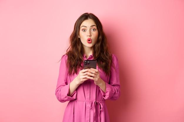 """Zdjęcie zdziwionej młodej kobiety, sapiącej i mówiącej """"wow"""", wpatrującej się w kamerę pod wrażeniem po przeczytaniu wiadomości online na telefonie komórkowym, stojącej ze smartfonem na różowej ścianie. skopiuj miejsce"""